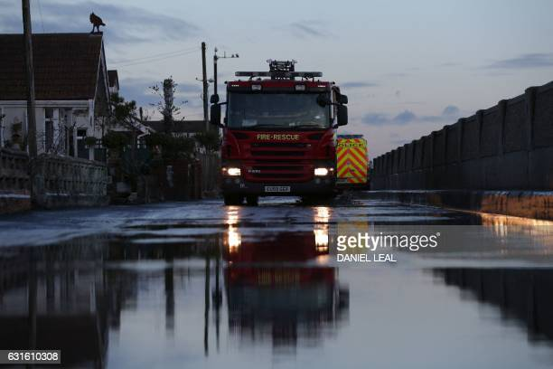A fire engine sits in a street as emergency services give information on flood risks to residents in Jaywick southeast England on January 13 2017...