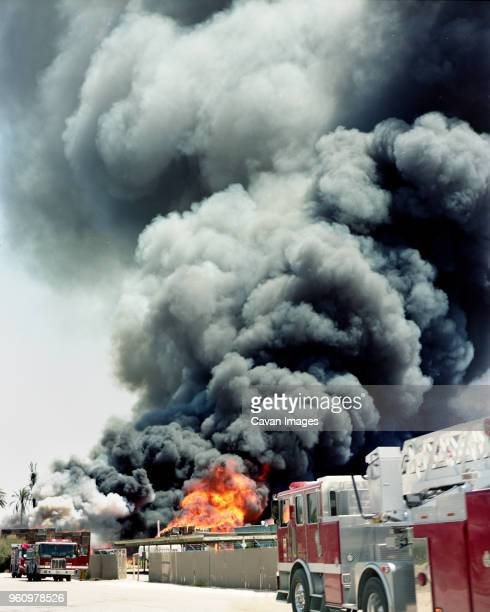 fire engines against smoke emitting from burning crates in factory - palm springs stock-fotos und bilder