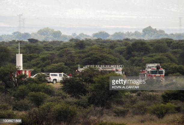 Fire engines are seen near the wreckage of a plane that crashed with 97 passengers and four crew on board on take off at the airport of Durango in...