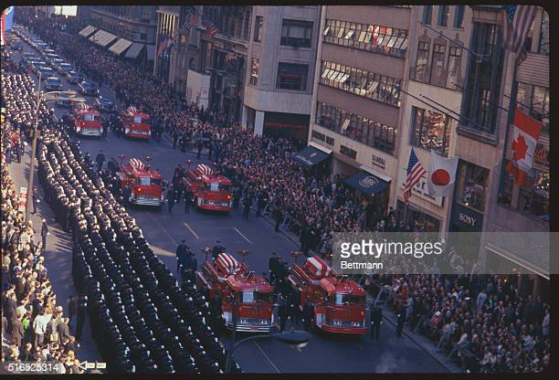 Fire engines carrying the bodies of ten of the twelve firemen who died in the Madison Square fire here 10/18 move slowly down Fifth Avenue 10/21 past...