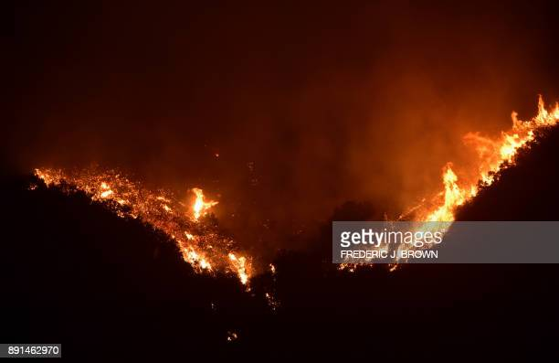 Fire erupts across a Romero Canyon hillside in Montecito California north of Santa Barbara on December 12 2017 Crews battling wildfires ravaging...