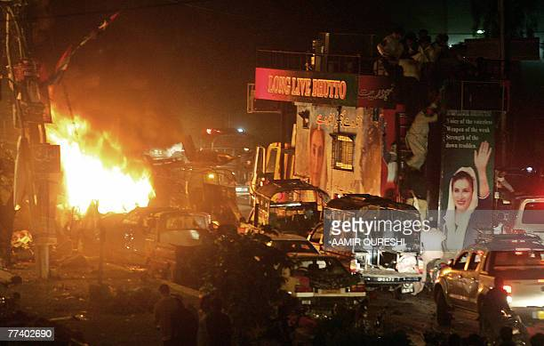 Fire erupts from a car in front of a vehicle carrying of former Pakistani prime minister Benazir Bhutto after bomb explosion in Karachi, 18 October...