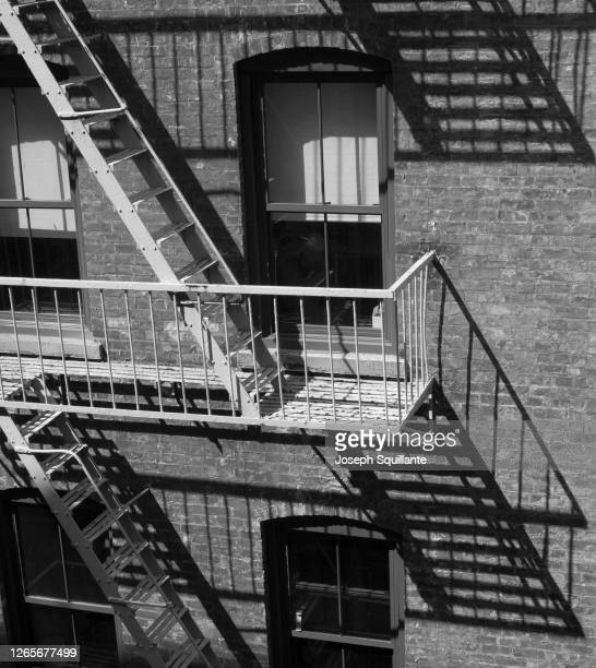 fire escape and shadows in the city - joseph squillante stock pictures, royalty-free photos & images