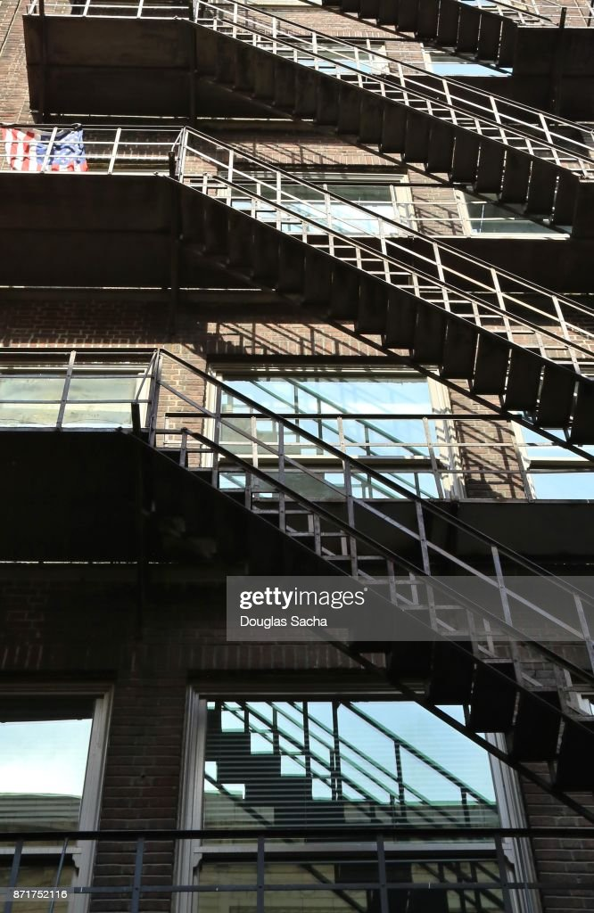 Fire Escape Platforms And Staircases Along The Exterior Highrise Building :  Stock Photo