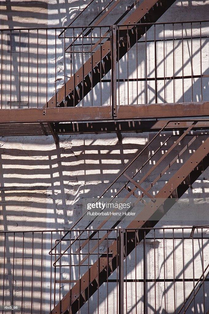 fire escape stairs and ladders cast parallel reflections against the white stucco of a building : Stockfoto