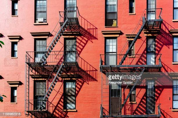 fire escape stairs on buildings in west village district, new york city - chelsea new york stock pictures, royalty-free photos & images