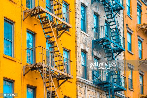fire escape stairs on typical buildings, new york city - chelsea new york stock pictures, royalty-free photos & images