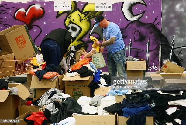 Fire evacuees sift through donated clothing at an Emergency Relief Centre in Edmonton Alberta on May 10 2016 Oil companies forced to halt production...