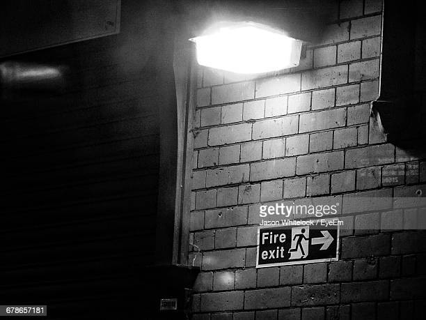 Fire Exit Sign On Wall Below Illuminated Street Light At Night