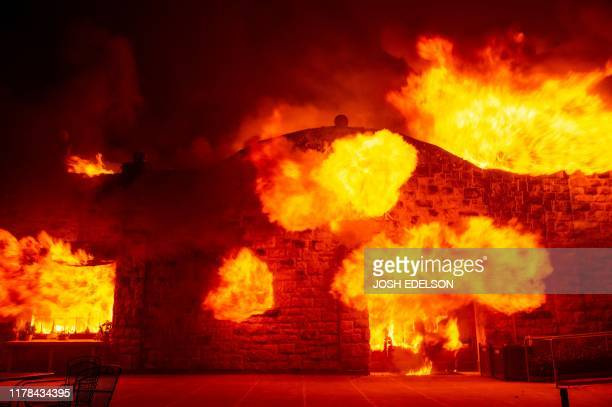 Fire explodes out the entrance of the Soda Rock Winery as it burns during the Kincade fire as flames race through Healdsburg California on October 27...