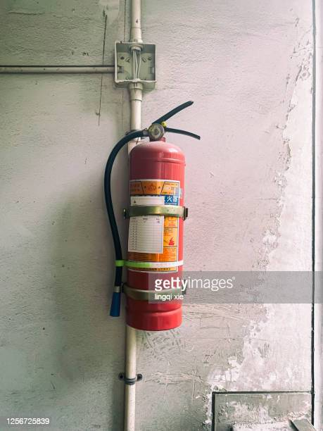 a fire extinguisher hangs on a dilapidated wall - industrial hose stock pictures, royalty-free photos & images