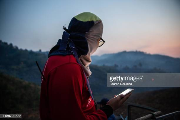 A fire fighter checks a location on his phone before heading to the scene of a forest fire on April 19 2019 in Chiang Rai Thailand Thailand's...