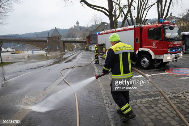 A fire fighter cleans the main road B416 after the Mosel flood inCochem Germany 08 January 2018 Decreasing water levels are expected later today...