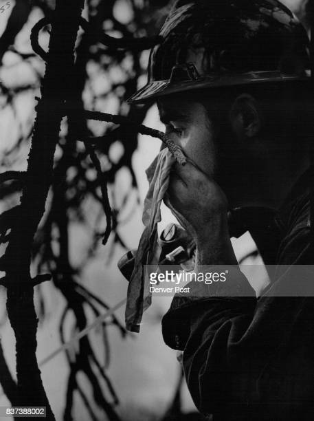 Fire fighter Jim Cicetti holds handkerchief to his nose to protect himself from the intense smoke at the blaze which damaged timber on private land...