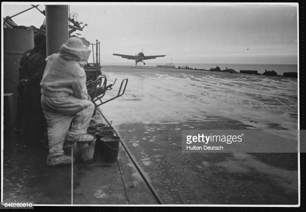 A fire fighter looks on as a Grumman Martlett fighter aircraft comes in to land on the flight deck of a Royal Navy aircraft carrier