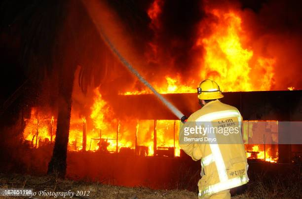 Fire Fighter makes attack on the rear of the building as fire rages on.