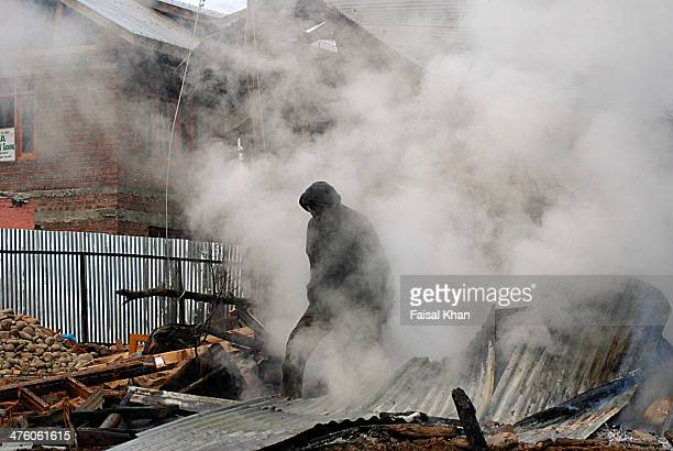 Fire fighter makes his way through the rubble of the houses damaged during a fierce gunfight between militants and Indian army in which one militant...