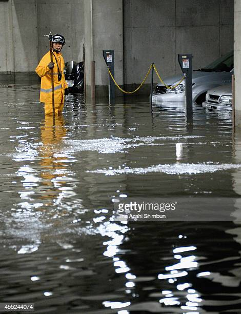 A fire fighter searches anyone missing at a flooded car park after torrential rain hitting Tokyo on September 10 2014 in Tokyo Japan
