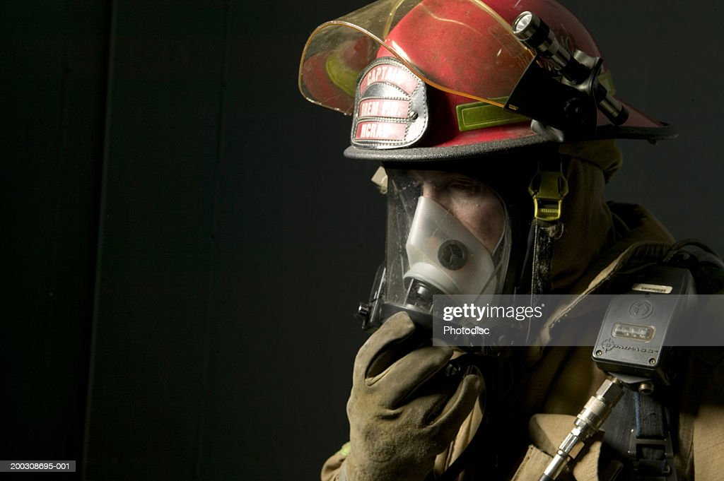 Fire fighter standing in uniform wearing face mask : Stock Photo