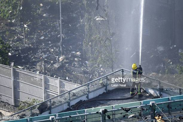 A fire fighter tackles the building after a huge fire engulfed the 24 storey residential Grenfell Tower block in Latimer Road West London in the...