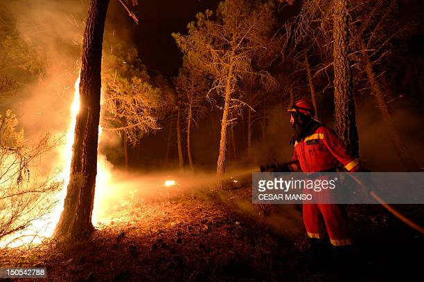 Fire fighter works at the site of a wildfire in Tabuyo del Monte, near Leon on August 21, 2012. Numerous wildfires have broken out across Spain in...