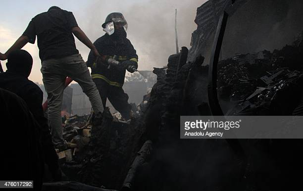 Fire fighters and locals try to extinguish the fire at Markato marketplace in Addis Ababa Ethiopia on June 5 2015