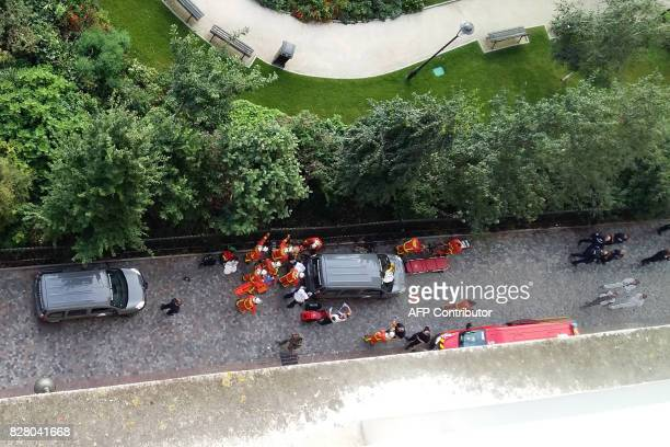 TOPSHOT Fire fighters and medics gives assistance to injured soldiers after a car slammed into them while on patrol in LevalloisPerret outside Paris...