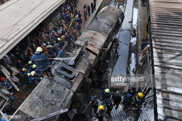 Fire fighters and onlookers gather at the scene of a fiery train crash at the Egyptian capital Cairo's main railway station on February 27 2019 The...