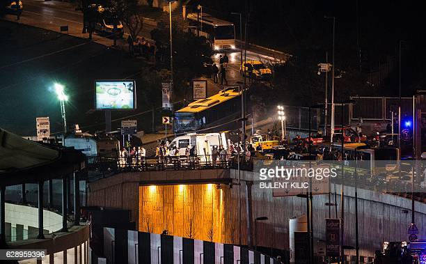 Fire fighters and police work at the site of a car bomb explosion outside the stadium of football club Besiktas in central Istanbul on December 10...