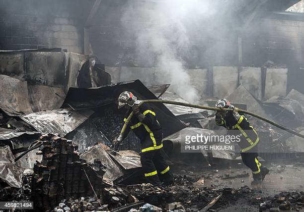 Fire fighters are at work to extinguish a fire that broke out on a warehouse belonging to French charity 'Restos du Coeur' on December 2 2014 in...