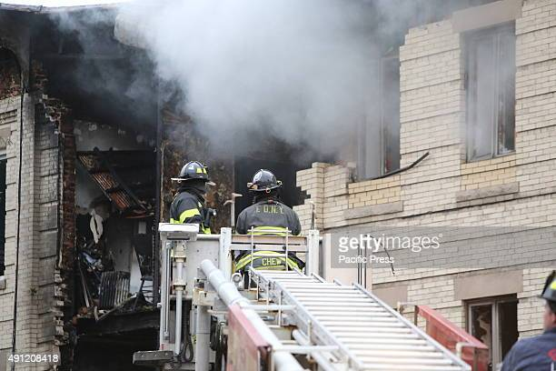 Fire fighters atop ladder contend with smoke Fire companies NYPD Red Cross and other emergency response personnel gathered in Borough Park along with...