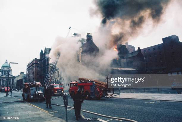 Fire fighters battle a blaze from an Irish Republican Army bomb attack Belfast Northern Ireland November 6 1971 The view looks along Linenhall Street...