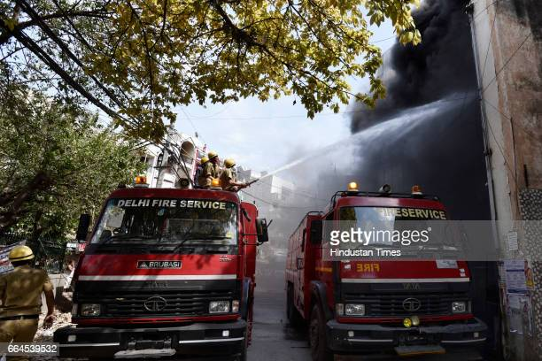 Fire fighters dousing flames after fire broke out in a decoration company at Jeewan Nagar on April 4 2017 in New Delhi India The employees rushed out...