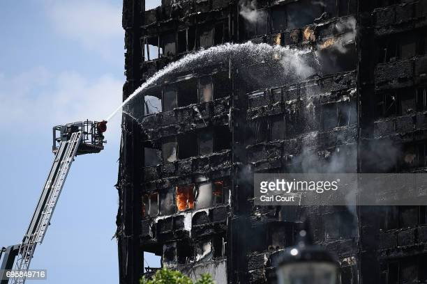 Fire fighters drench the burning 24 storey residential Grenfell Tower block in Latimer Road West London on June 14 2017 in London England The Mayor...