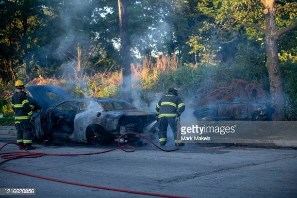 Fire fighters extinguish a car and sofa during widespread unrest following the death of George Floyd on May 31 2020 in Philadelphia Pennsylvania...