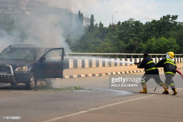 Fire fighters extinguish a fire coming out from a vehicle following clashes between security operatives and supporters of an imprisoned leader of the...