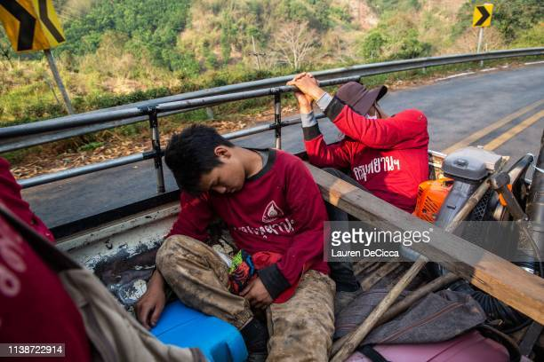 Fire Fighters from Doi Mae Salong Station nap on their drive back to their station after a long day of work on April 20 2019 in Chiang Rai Thailand...