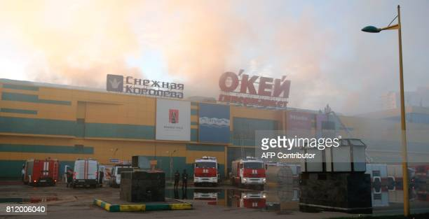 Fire fighters gather around the Rio shopping mall in Moscow on July 10 2017 Ten people poisoned by smoke were hospitalised after a fire broke out in...