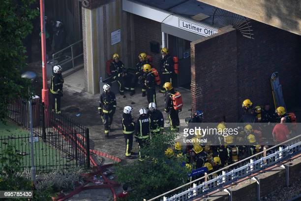 Fire fighters gather at the building after a huge fire engulfed the 24 storey residential Grenfell Tower block in Latimer Road West London in the...