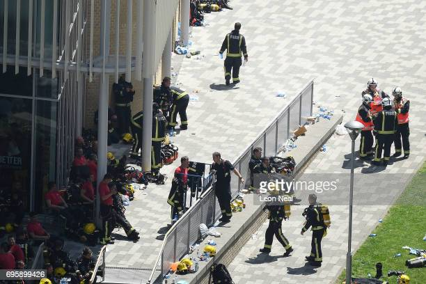 Fire fighters gather near the burning 24 storey residential Grenfell Tower block in Latimer Road West London on June 14 2017 in London England The...