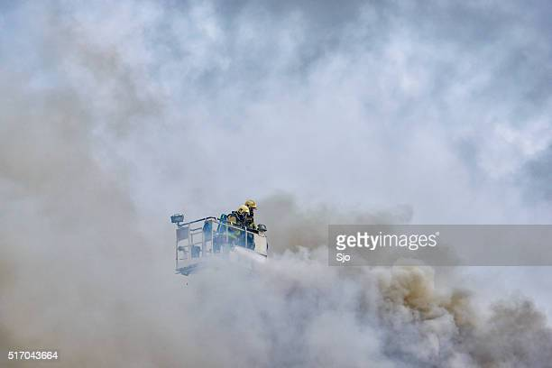 Fire fighters in smoke high up in the air