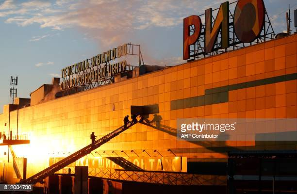 Fire fighters inspect a wall as smoke rises from the Rio shopping mall in Moscow on July 10 2017 Ten people poisoned by smoke were hospitalised after...