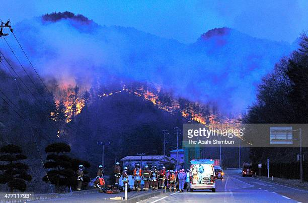 Fire fighters only look up the mountain fire expanding after a 9.0 magnitude strong earthquake and subsequent tsunami struck on March 13, 2011 in...