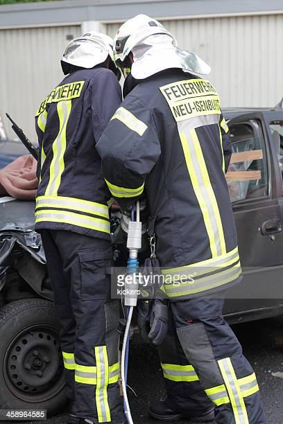 Fire fighters opening jammed car door with spreader