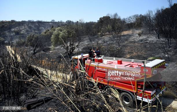 Fire fighters patrol after a brushfire hit the countryside around Saint Gilles on June 29 2019 in the south of France
