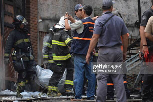 Fire fighters put out a fire in a house where a small plane crashed in the northern suburbs of Sao Paulo Brazil on March 19 2016 Seven people were...