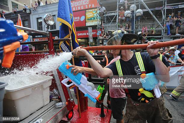 TORONTO ON JULY 3 Fire fighters reload their water reservoirs during the the 2016 Toronto Pride parade along Yonge Street in Toronto July 3 2016