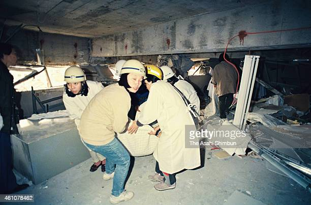 Fire fighters rescue a patient from the crumpled 4th floor of the Kobe City Medical Center West Hospital on January 17 1995 in Kobe Hyogo Japan...