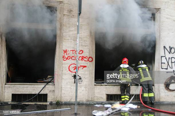 Fire fighters seen extinguishing a burning building after the clashes Cars were burned and shops destroyed during the clashes between the protesters...