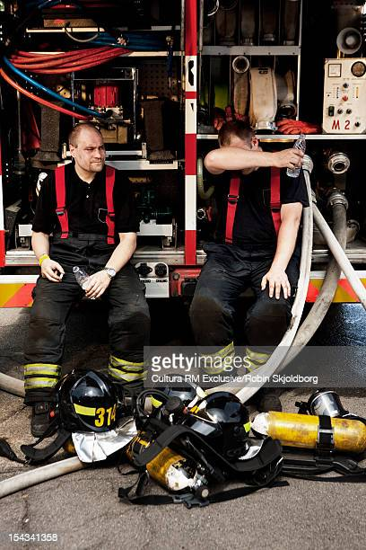 Fire fighters sitting on truck